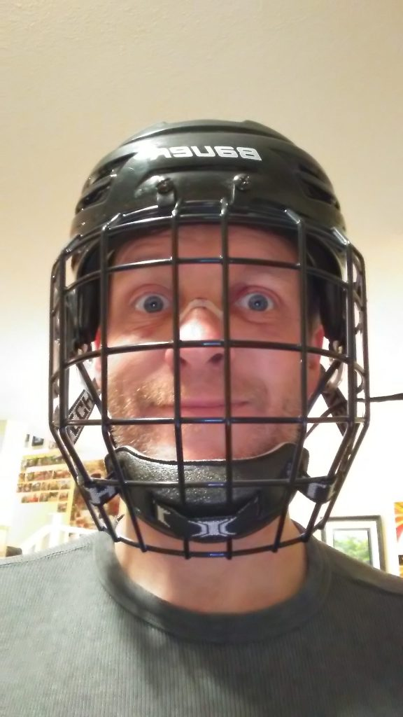 Mark wearing a hockey helmet and mask with bandaid on cut nose