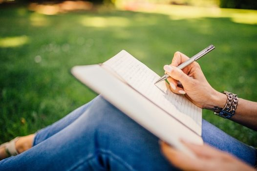 girl writing in notebook outdoors