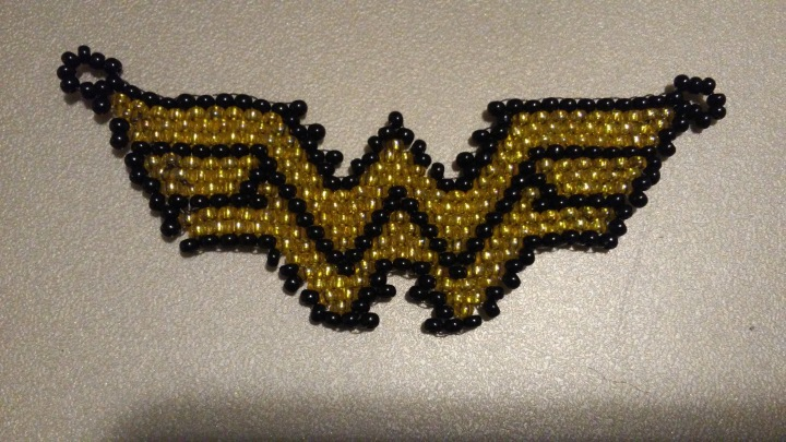 gold and black Wonderwoman symbol pendant made from seed beads