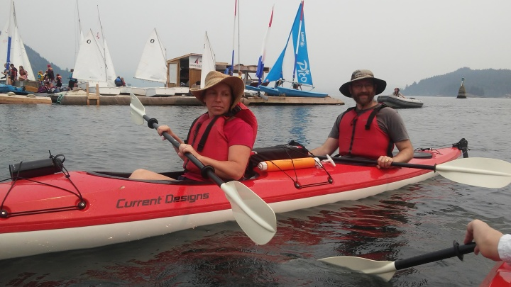 Sheila and Emile kayaking with sailboats on dock in background